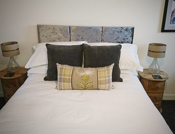 Craigmonie B&B Stag room, view of a bed and lamps standing on a stylish circle bedside tables