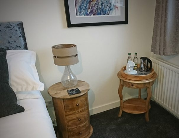 B&B Stag room, view of the bed and stylish old fashioned furniture bedside table with lamp on it