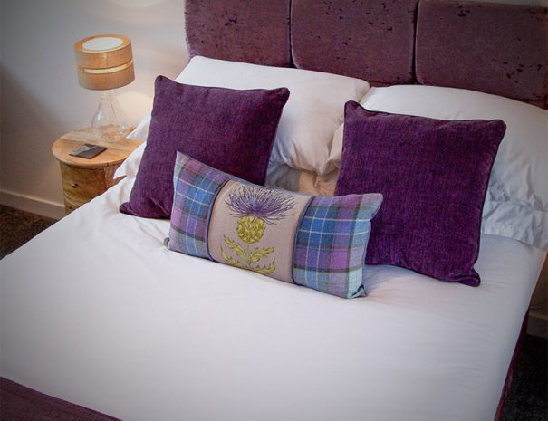Craigmonie B&B Highland Cow, view of a bed and lamp standing on a stylish circle bedside table