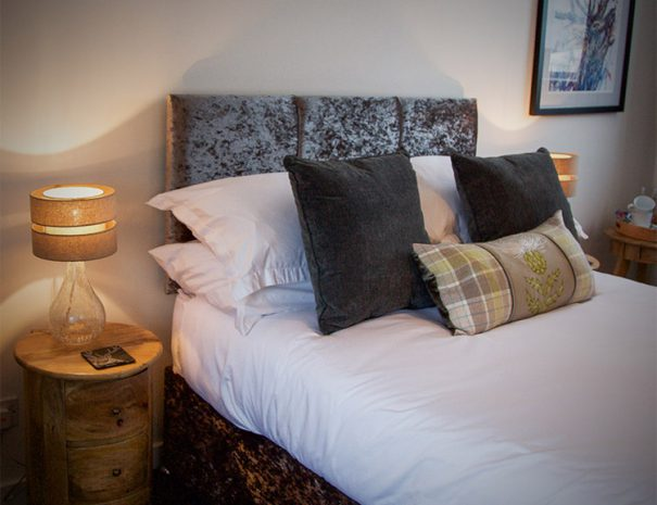 Craigmonie B&B Stag room, view of a bed and lamp standing on a stylish circle bedside table