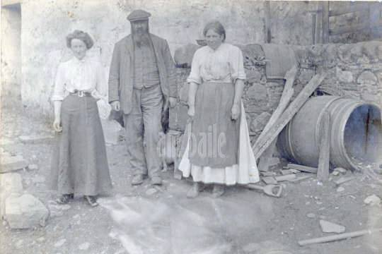 Old photo of three people standing next to a barrel